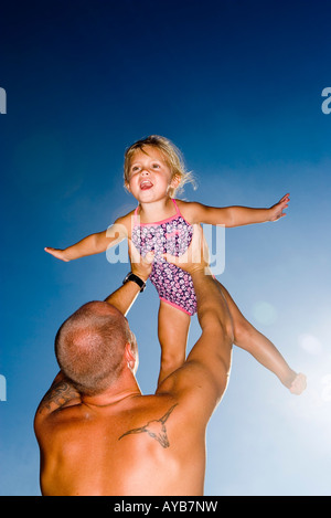 Young father holding daughter up in the air - Stockfoto