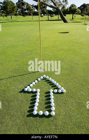 An arrow pointing to a hole on a golf green - Stock Photo