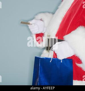 Santa Claus holding shopping bag and credit card - Stock Photo