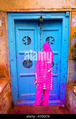 Woman in Old Delhi by a colorful door, India - Stock Photo