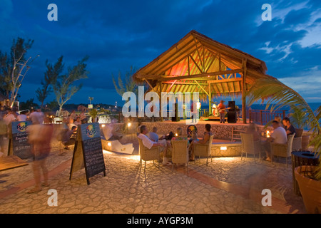 Jamaica Negril Ricks Cafe open air bar viewpoint at sunset Reggae band playing - Stock Photo