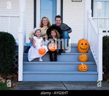 Family with daughters dressed in witch and princess Halloween costumes - Stock Photo
