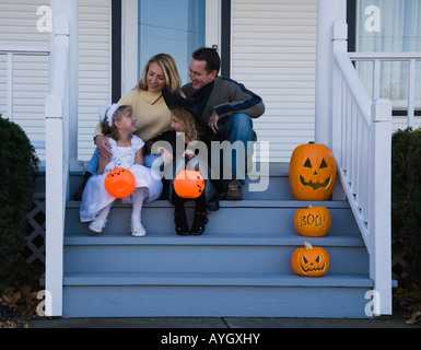 Family with daughters dressed in witch and princess Halloween costumes - Stockfoto