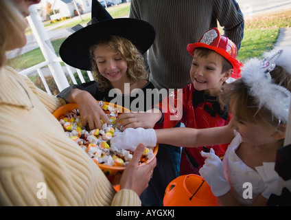 Children in Halloween costumes reaching into bowl of candy - Stock Photo