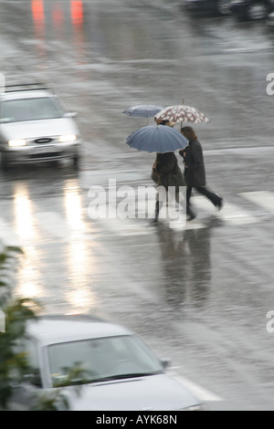 people with umbrellas crossing road in rain - Stock Photo