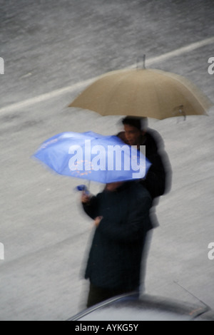 people crossing road with umbrella in rain - Stock Photo