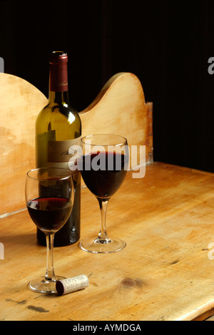 Glasses of Red Wine Bottle on Antique Pine Chest - Stock Photo