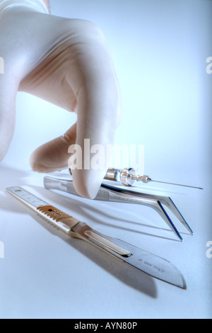 Hand picking up scalpel - Stock Photo