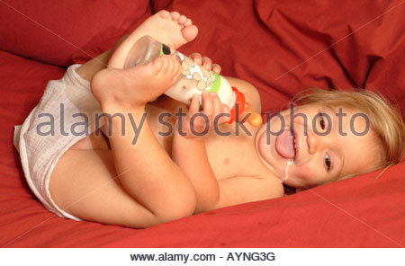 Happy baby laughing drinking milk plastic bottle lying red bed wearing cloth nappy feet holding bottle full length - Stock Photo