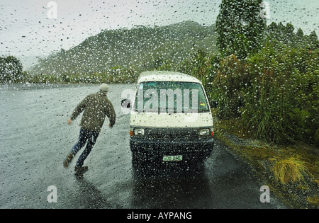 A man, caught out in a sudden rainstorm, running for shelter in his van. Seen through a rain-spattered window - Stock Photo