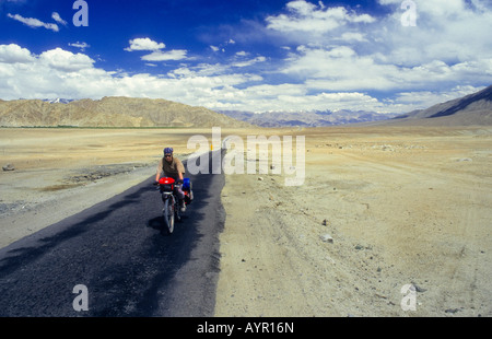 Cyclist wearing head covering riding fully-loaded bike down a lonely stretch of desert highway, Ladakh, India - Stock Photo