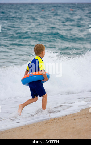 Five-year-old boy wearing flotation tire and wetsuit running along the beach in Marina di Orosei, Sardinia, Italy - Stock Photo