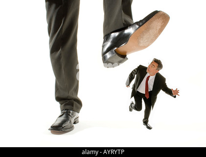 Giant foot stepping on a kneeling businessman running away - Stock Photo