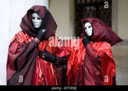 Two people wearing red-and-black costumes, hooded cloaks and masks, Carnevale di Venezia, Carneval in Venice, Italy - Stock Photo