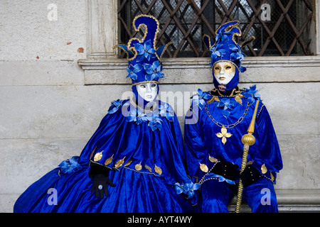 Two people wearing blue costumes and masks sitting on a bench in front of a window, Carnevale di Venezia, Carneval - Stock Photo