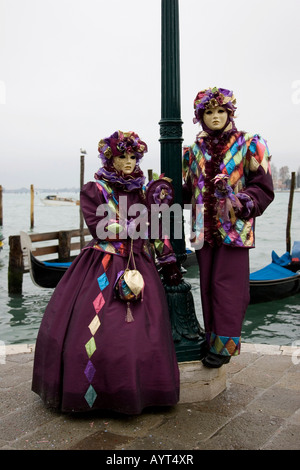 Two people wearing purple costumes and masks standing in front of gondolas, Carnevale di Venezia, Carneval in Venice, - Stock Photo