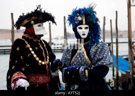 Two colourful costumes and masks, Carnevale di Venezia, Carneval in Venice, Italy - Stock Photo