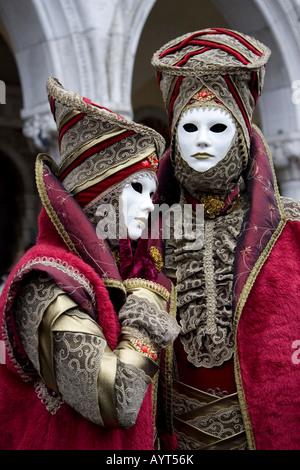 Two red costumes and masks, Carnevale di Venezia, Carnival in Venice, Italy - Stock Photo