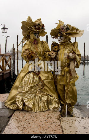 Two golden costumes and masks, Carnevale di Venezia, Carneval in Venice, Italy - Stock Photo