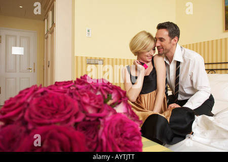 Couple on bed, bunch of roses in foreground - Stock Photo