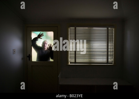 Man looks into room through frosted glass window pane on door beside window with blind - Stock Photo