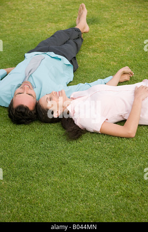 Couple lying on grass - Stock Photo