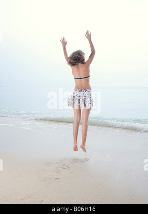 Young girl makes joy jumps on the beach - Stock Photo