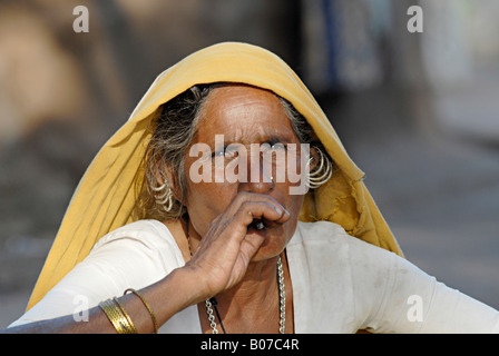 Close-up of an old tribal woman smoking bidi, an Indian handmade cigarette made of tobacco or beedi leaves. Bhil - Stock Photo