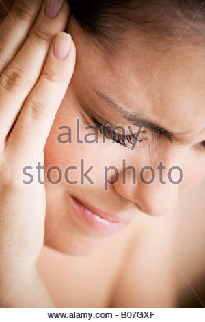 Woman with toothache or headache, holding her hand to her temple - Stock Photo