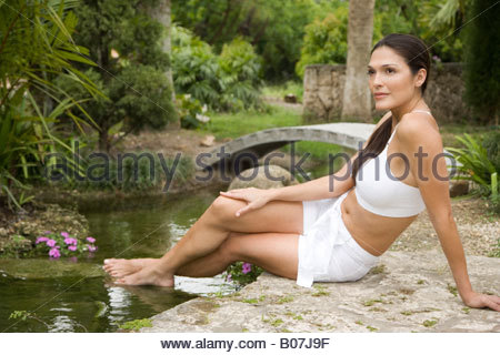 Portrait of a woman sat by a pond in an oriental garden - Stock Photo