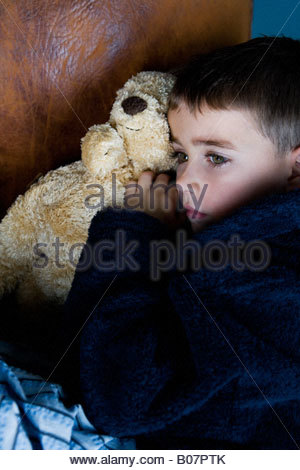 little boy snuggling up with teddy bear - Stock Photo