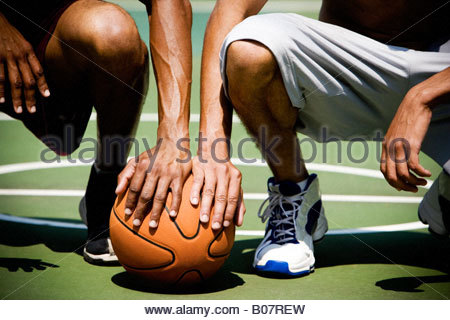 Two  African American kneeling side by side on an urban basketball court, close up - Stock Photo