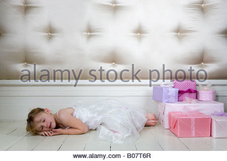 Little girl asleep on the floor next to her birthday presents - Stock Photo