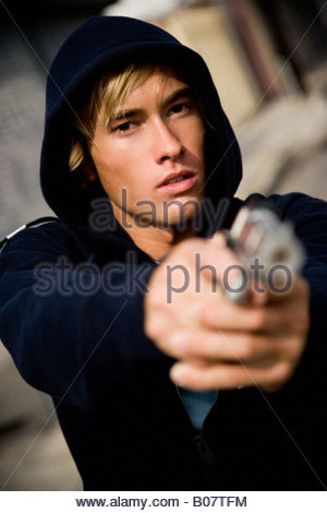Portrait of a young man holding a gun - Stockfoto