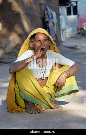 Old tribal woman smoking bidi, an Indian handmade cigarette made of tobacco or beedi leaves. Bhil tribe - Stock Photo