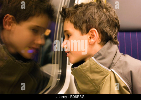 Young boy on train looking out of window - Stock Photo