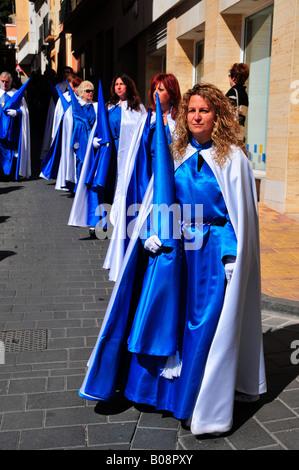 Women dressed in penitential robe (nazarenos), Semana Santa, Holy Week procession in La Nucia, Costa Blanca, Spain - Stock Photo