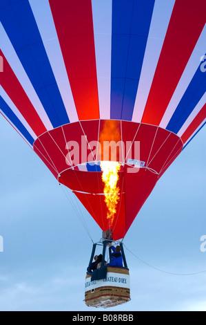 Hot air balloon ascending, International Balloon Festival in Château-d'Oex, Vaud, Switzerland - Stock Photo