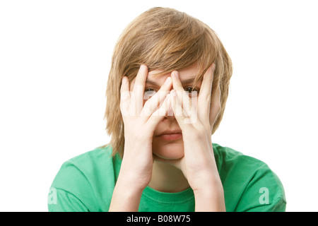 13-year-old hoy covering his face with his hands - Stock Photo