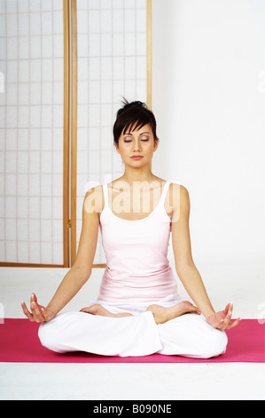 Young woman sitting in lotus position, meditating - Stock Photo