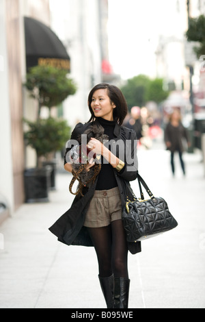A young woman is walking through a crowded city street holding a canine companion. - Stock Photo