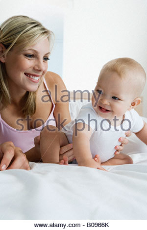 Young mother playing with baby (6-12 months) in bedroom - Stock Photo