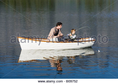 Father and son (4-7) sitting in rowing boat on lake, fishing with fishing rod - Stockfoto