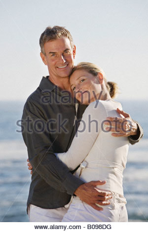 Mature couple embracing on beach, smiling, portrait - Stock Photo