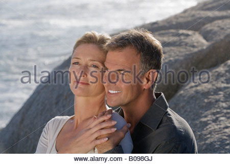 Mature couple sitting on rocks, embracing and enjoying view of coastline - Stock Photo