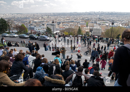 Tourists sitting on the steps of the Basilica of Sacre Coeur overlooking Paris - Stock Photo