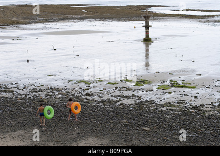 Two teenagers in swim suits stepping across a stony beach carrying swimming rings towards the sea - Stock Photo
