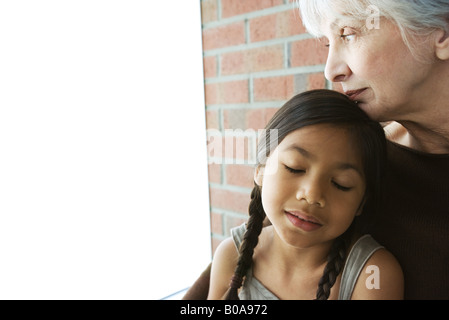 Senior woman resting her chin on granddaughter's head, girl's eyes closed - Stock Photo
