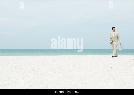Businessman walking across beach, carrying briefcase - Stock Photo