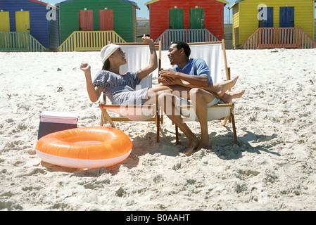 Couple sitting in lounge chairs at the beach, smiling, woman's legs on man's lap - Stockfoto